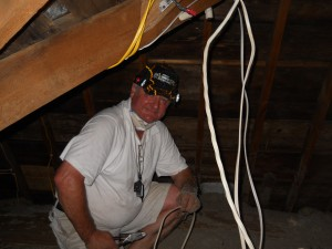 Electrical Contractor Works In The Hot Summer Attic